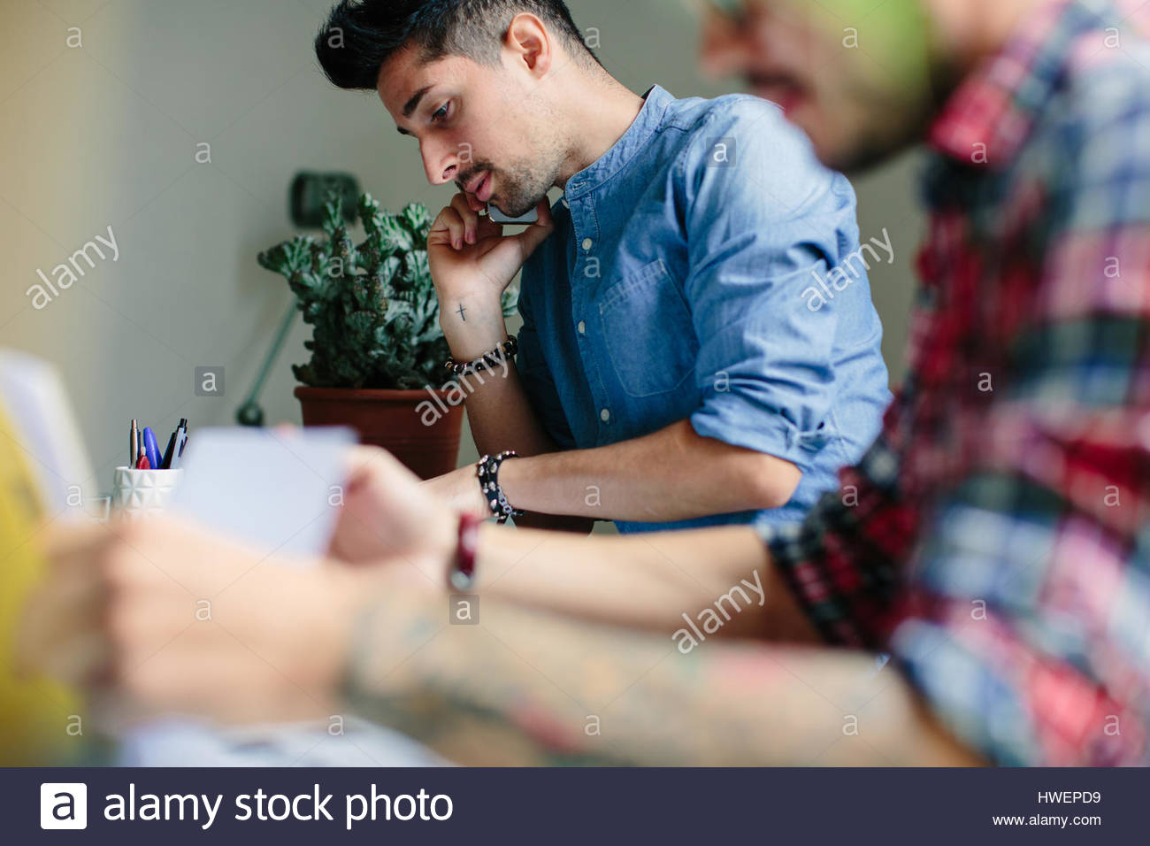 Male couple working at home together, sitting at desk, using smartphone - Stock Image