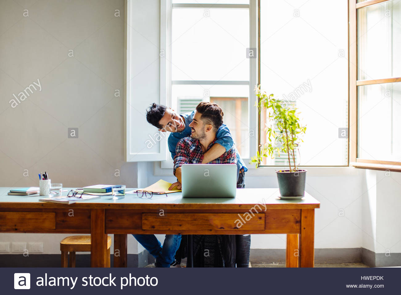 Male couple at home, man sitting at table using laptop, partner hugging him - Stock Image
