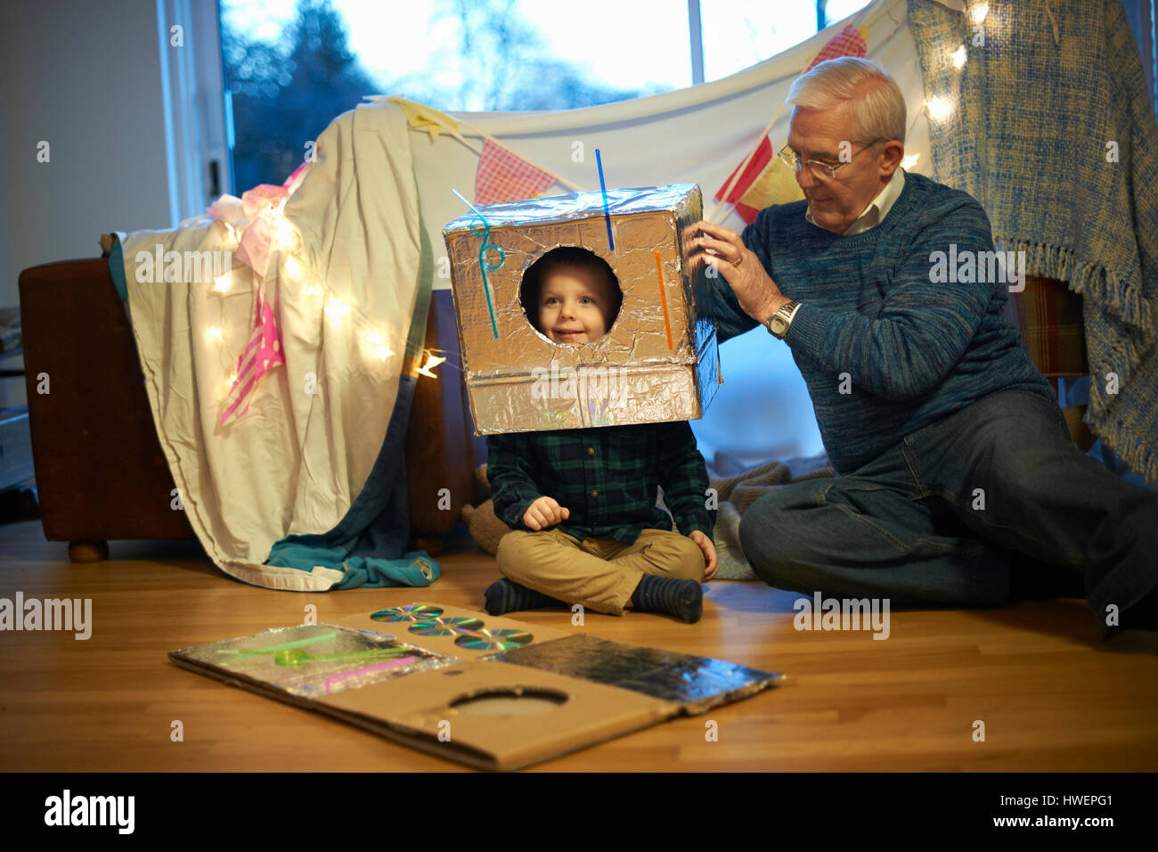 Senior man putting robot costume on grandson - Stock Image