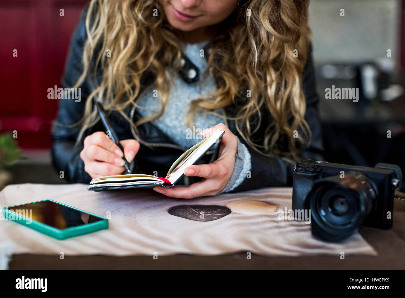 Woman at cafe writing in notebook Stock Photo