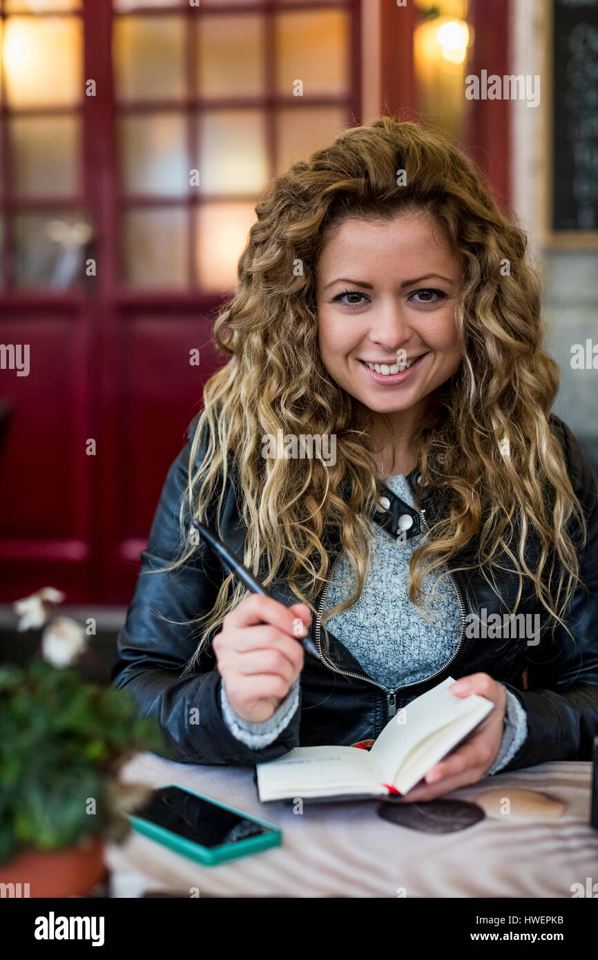 Woman at cafe writing in notebook - Stock Image