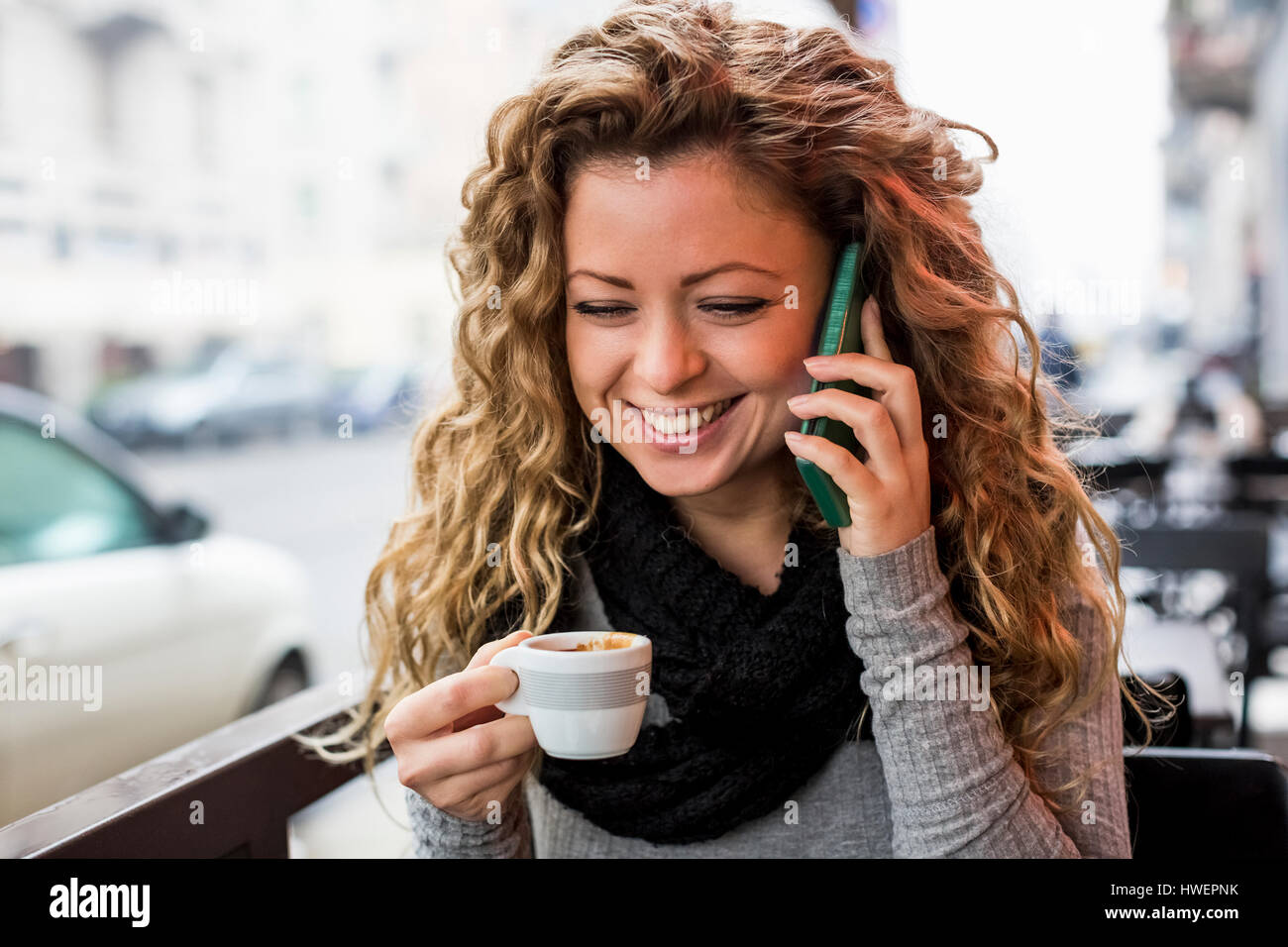 Woman in cafe holding espresso cup making telephone call smiling - Stock Image