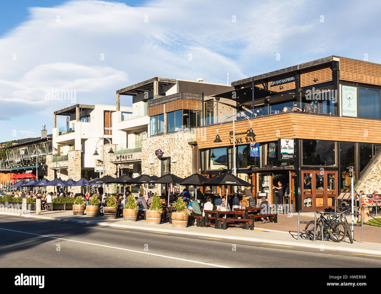 WANAKA, NEW ZEALAND - MARCH 5, 2017: Tourists and locals enjoy a drink on the trendy sidewalk bar and restaurants - Stock Image