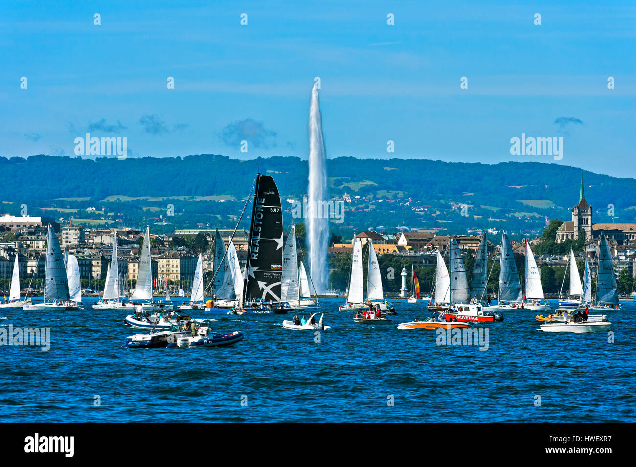 Sailing boats at the lakefront of Lake Geneva, behind fountain Jet d'eau and the St. Pierre Cathedral, Geneva, - Stock Image