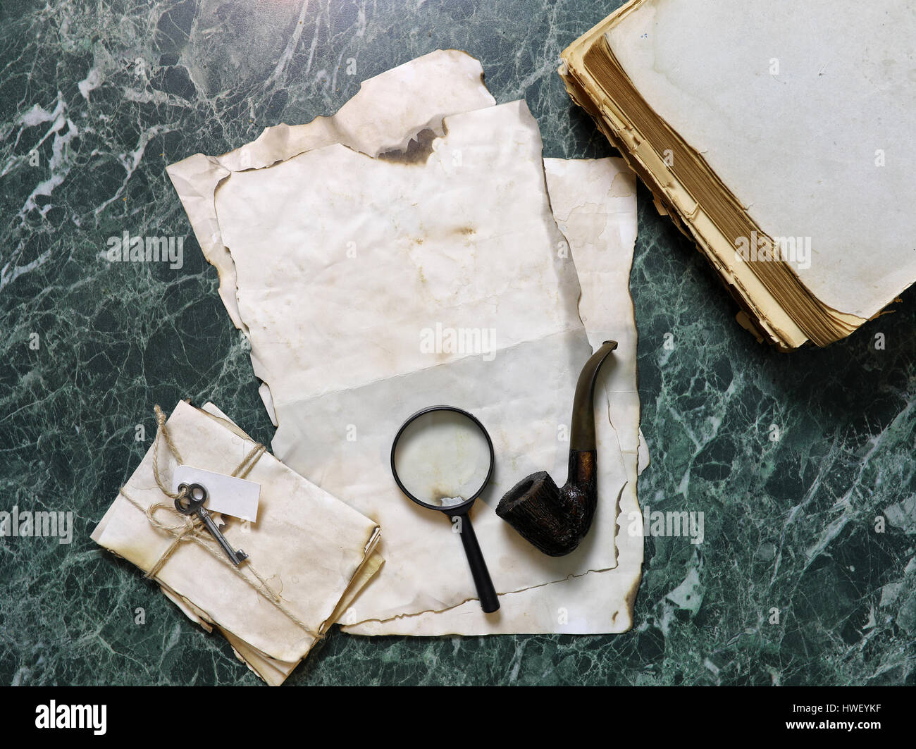 retro papers and book on detective work table with tools  - Stock Image