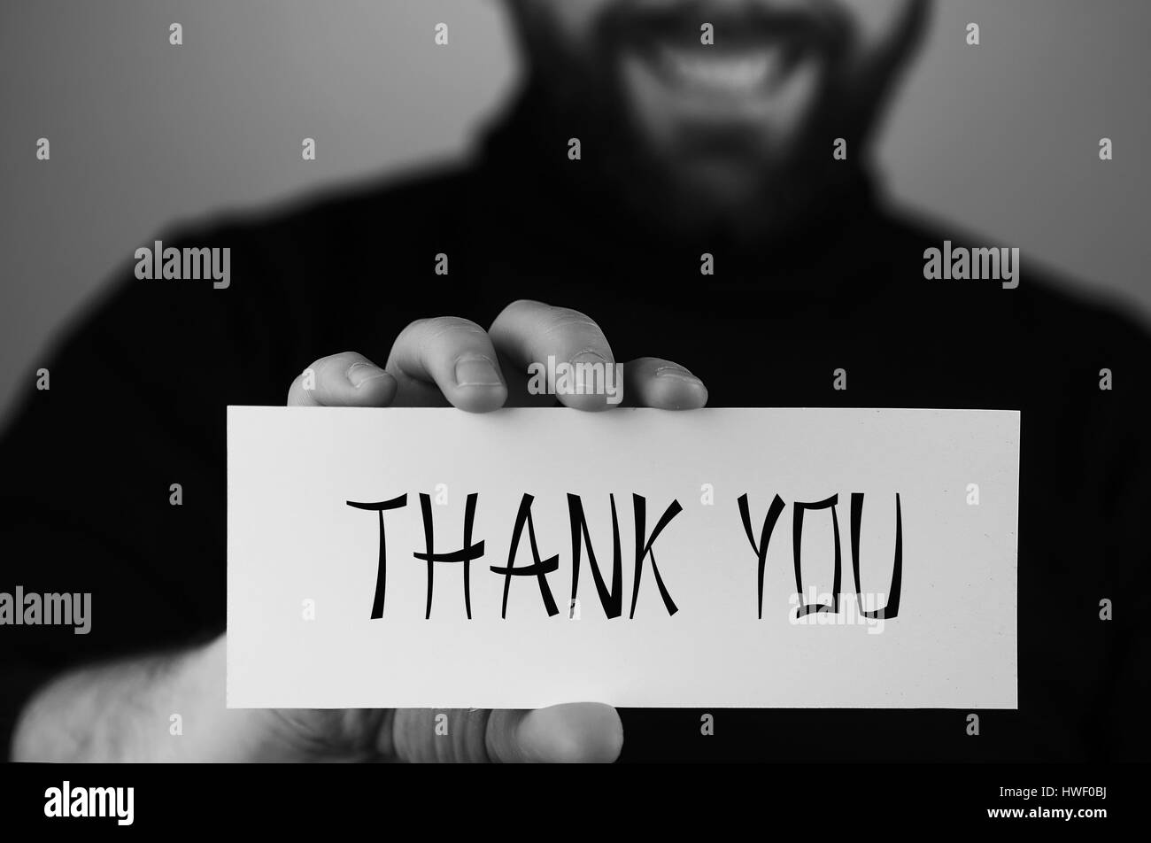 thank you on small white piece of paper in his hand man monochro - Stock Image
