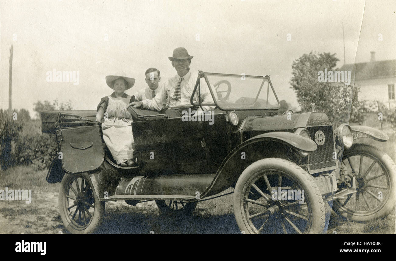 Antique c1915 photograph, two men and a woman in a c1915 touring Ford, with advertising for Swinehart Tires on the - Stock Image