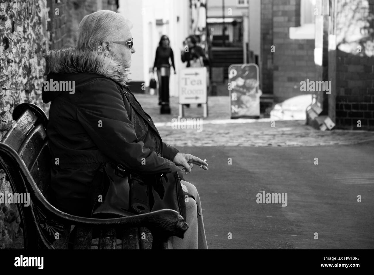 An elderly woman sitting on a bench smoking a cigarette. - Stock Image