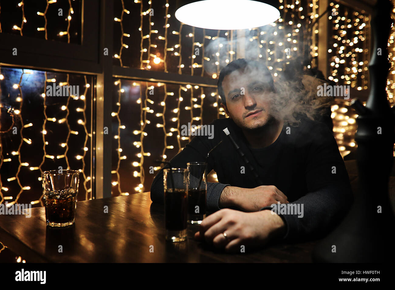 man holding hookah pipe and smoking in a night club  - Stock Image