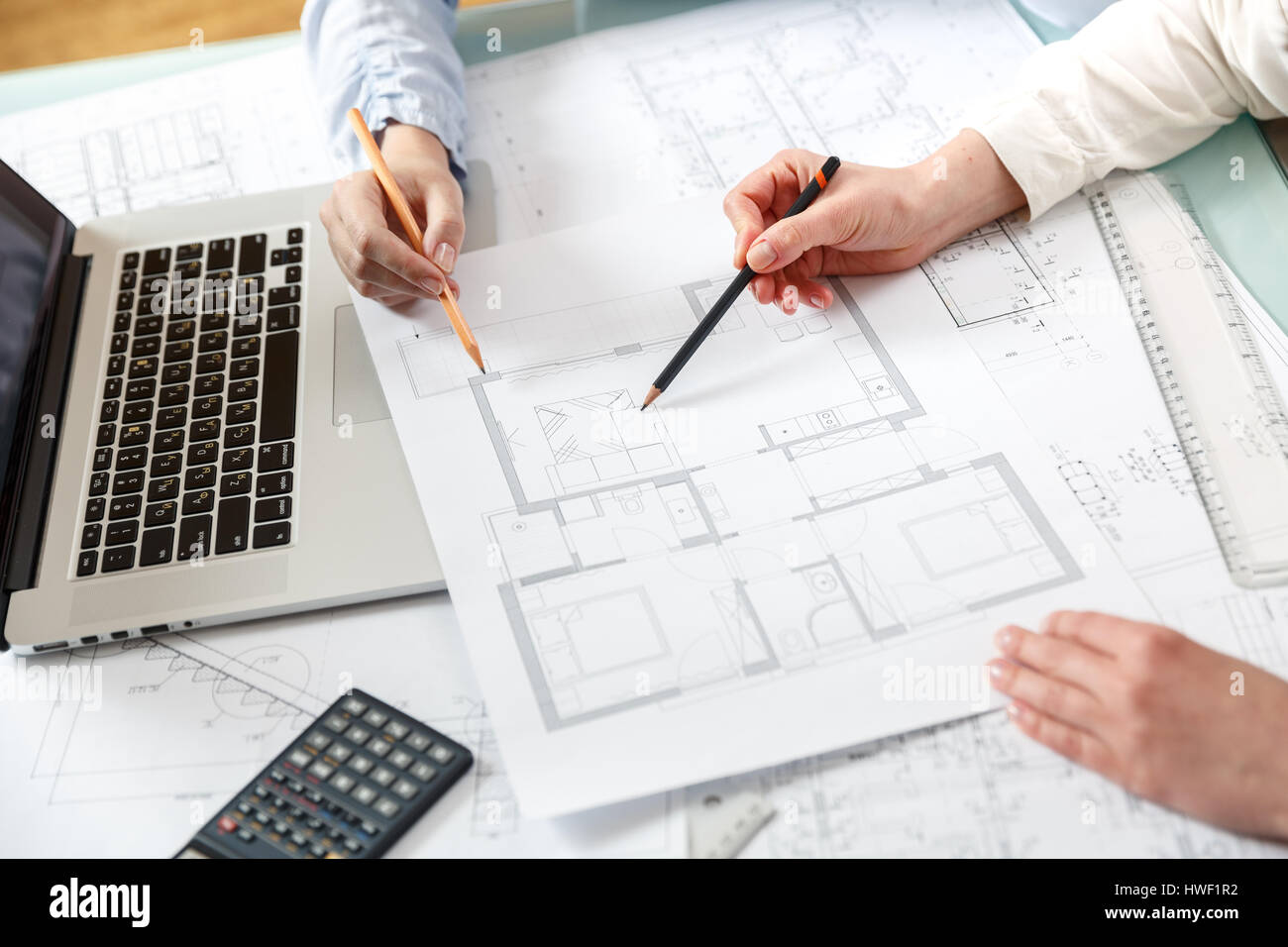 Young female architect and designer work and discuss details of a young female architect and designer work and discuss details of a blueprint project of new apartments photo concept of work on technical drawings malvernweather Image collections