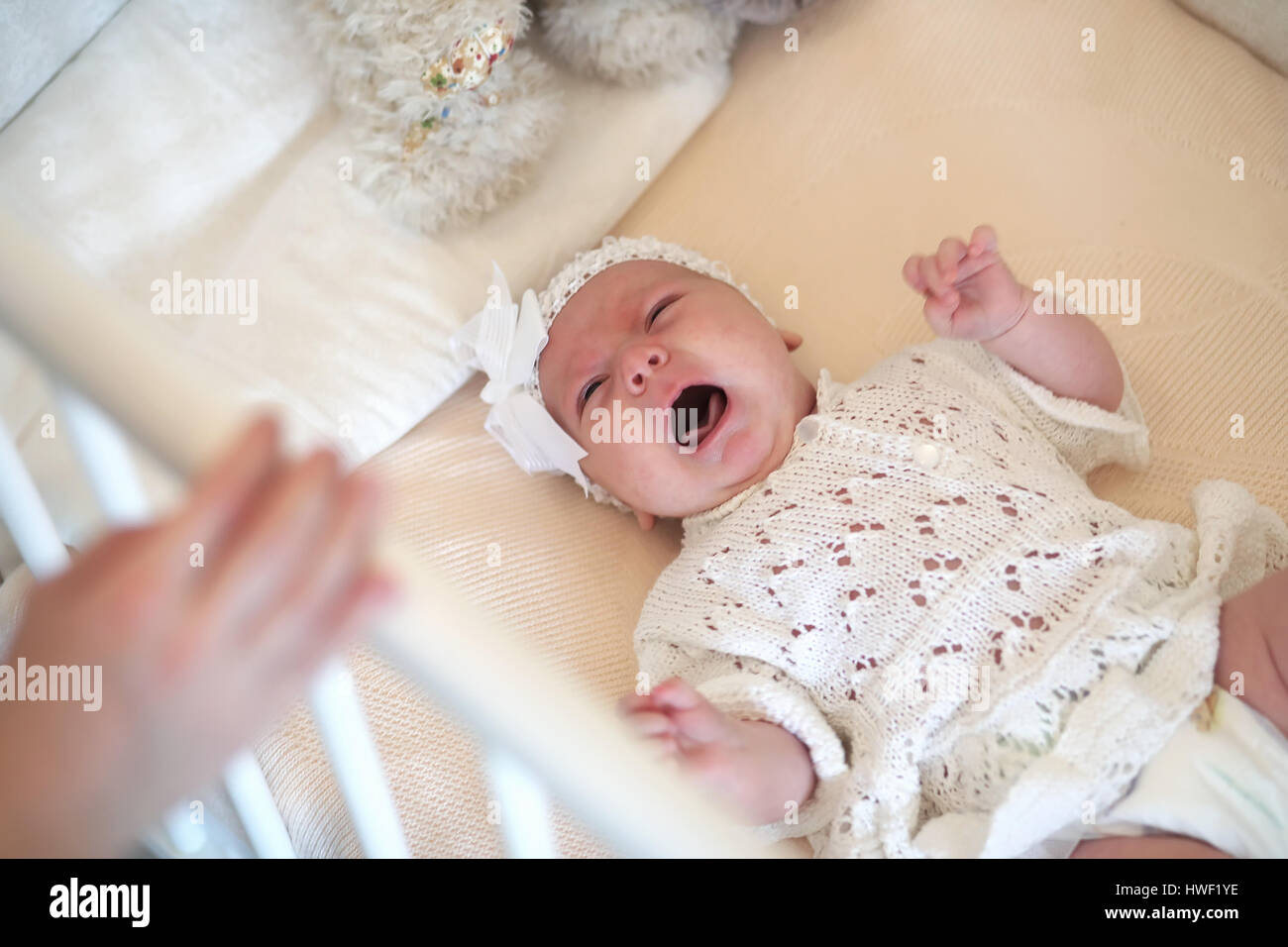 Cute newborn baby lies in the crib and looking mother Stock Photo