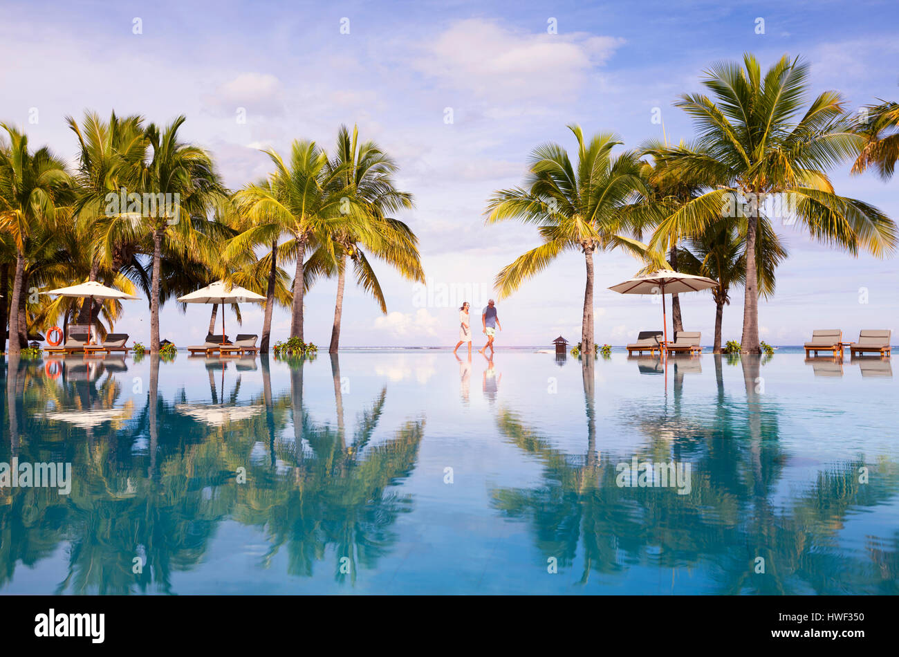 Honeymooners walking neer swimming pool. Luxurious five stars holiday resort on tropical paradise island - Stock Image