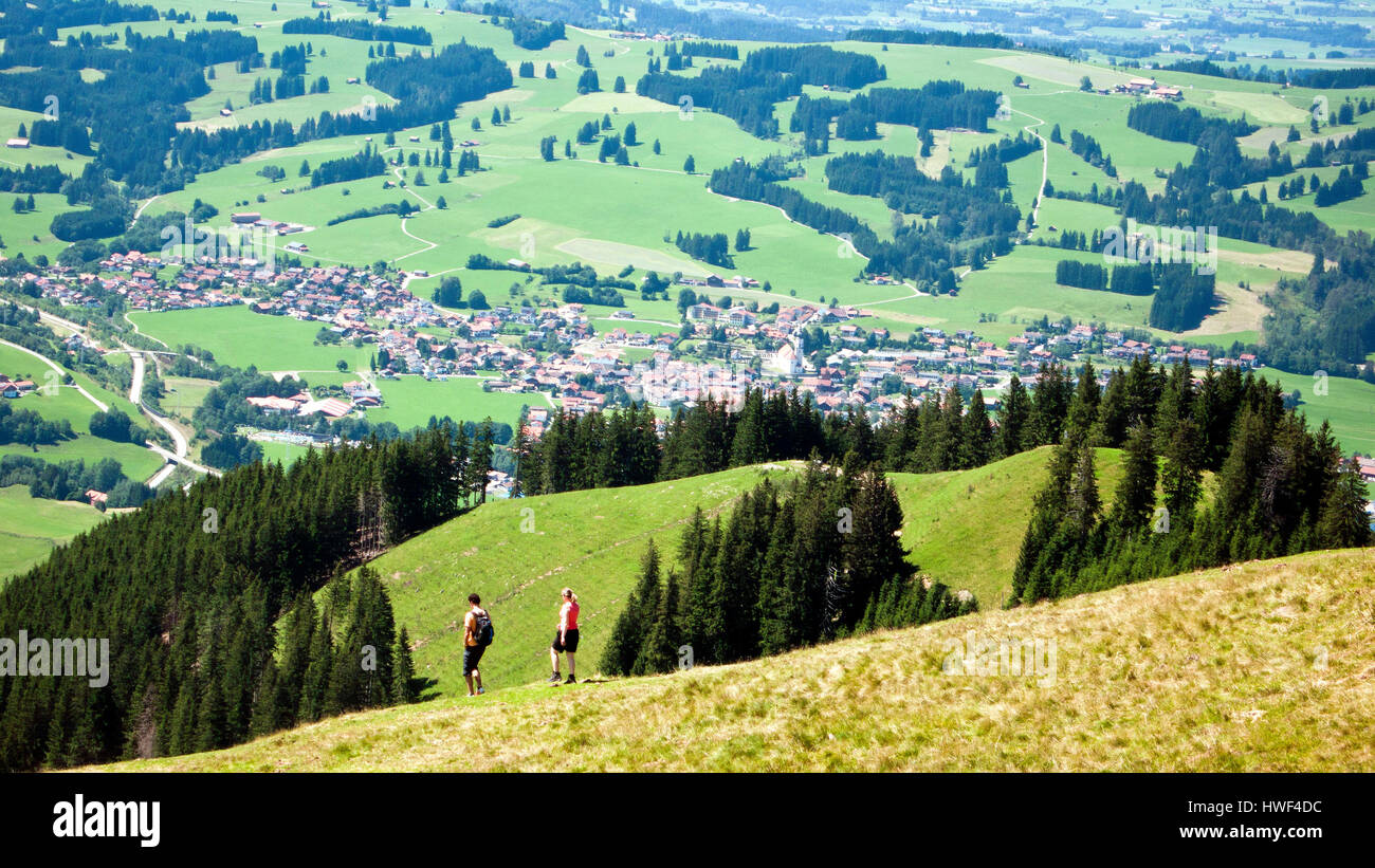Hikers descending the Reuterwanne with the village of Wertach in the background, Oberallgaeu, Germany. - Stock Image