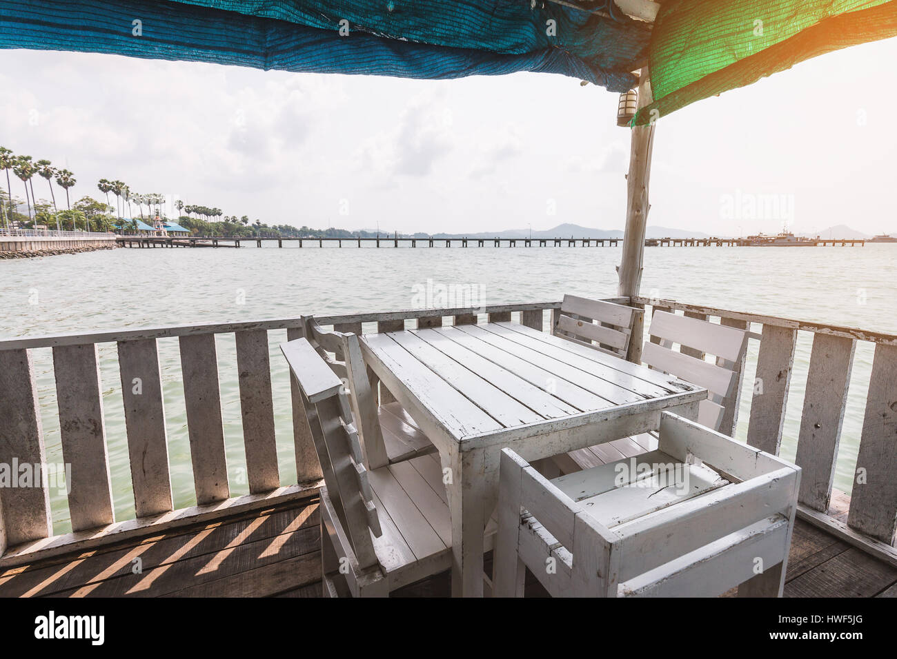 White Dining Table On Corner Of Indoor Beach Terrace Over Water Surface.  Terrace Surrounded By Wooden Wall And Covered By Colorful Canvas
