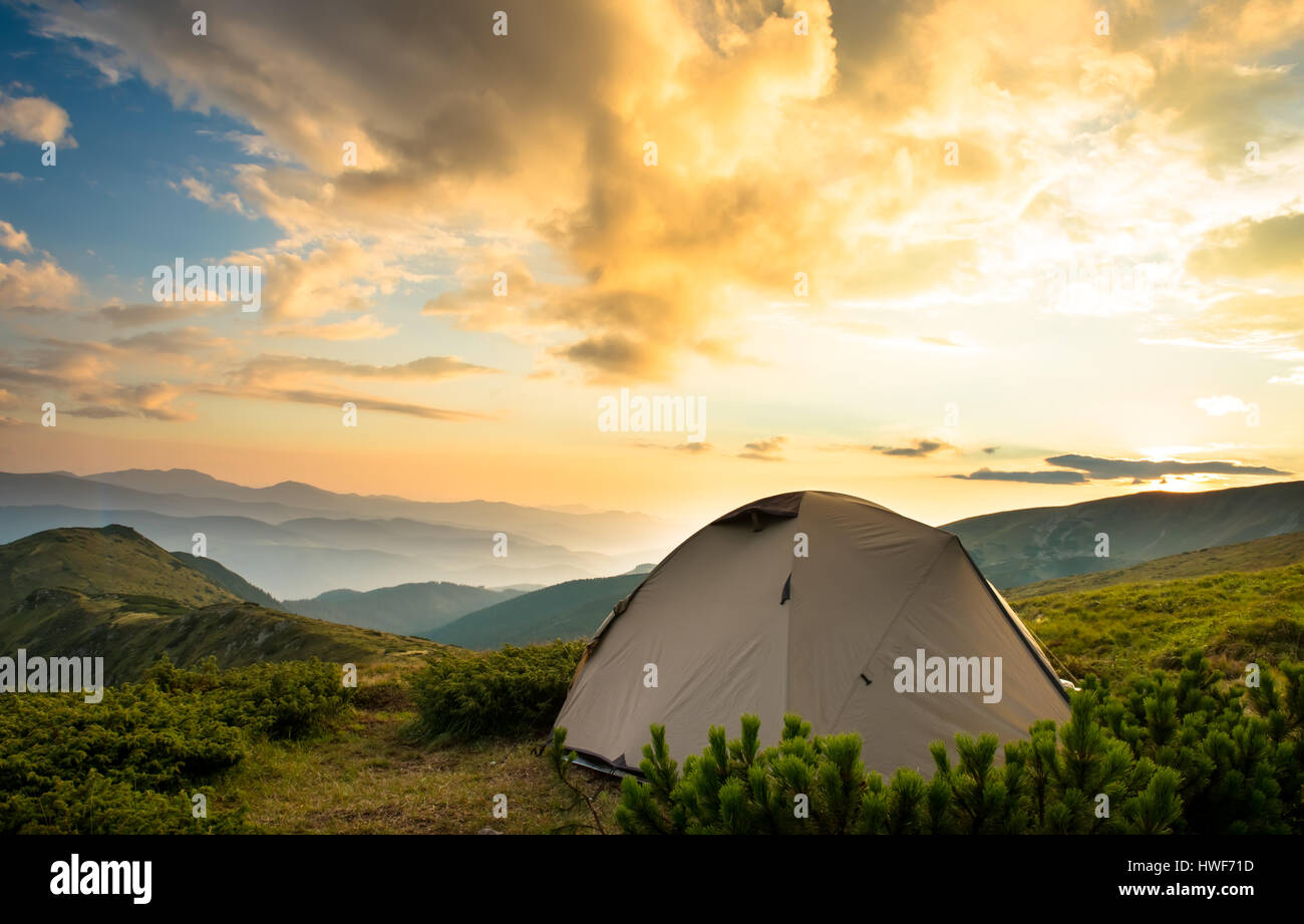Tourist tent in hight mountains summer sunset - Stock Image