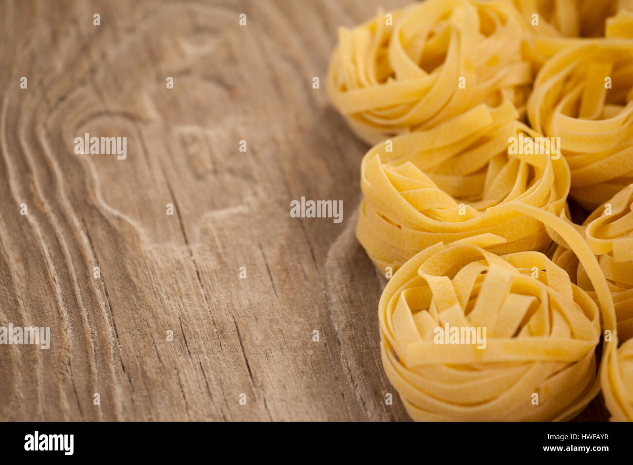 Fettuccine pasta arranged in a row on wooden background Stock Photo