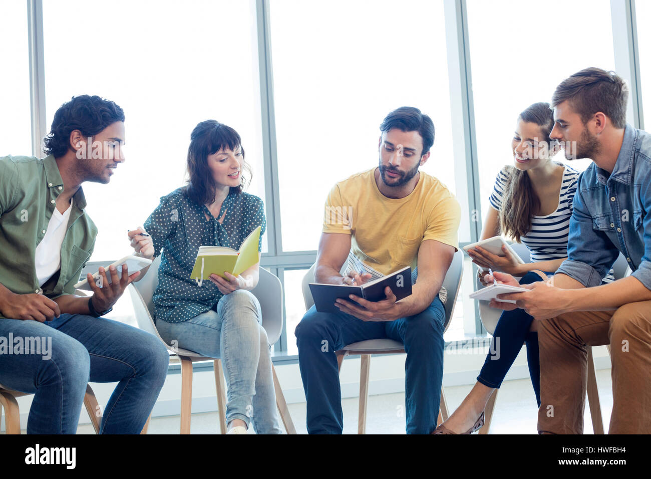 Creative business team discussing with their diaries in office - Stock Image