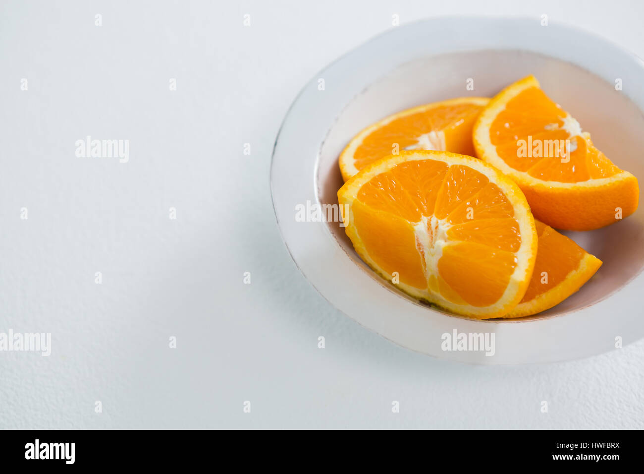 Close-up of oranges slices in bowl on white background - Stock Image
