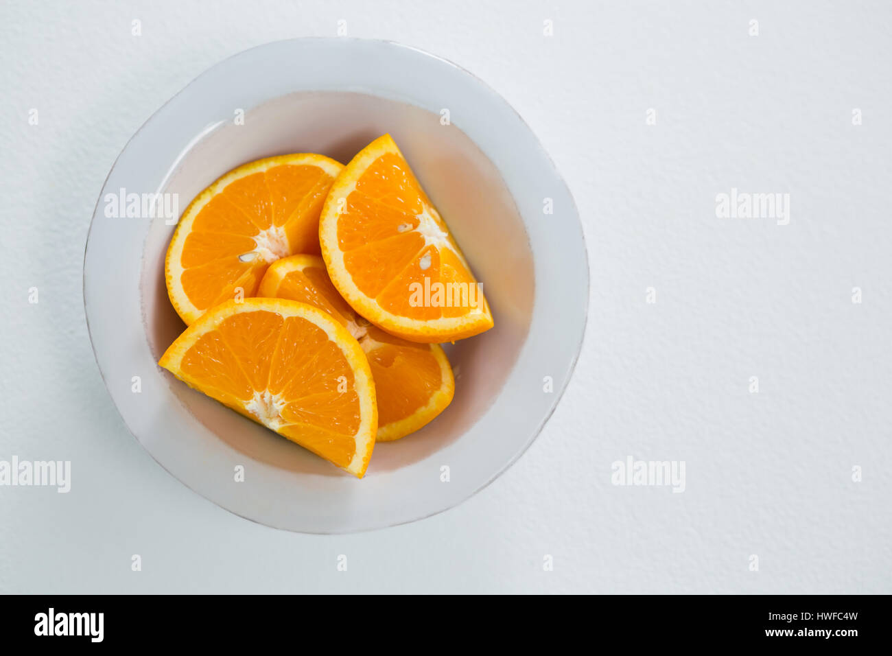 Overhead of oranges slices in bowl on white background - Stock Image