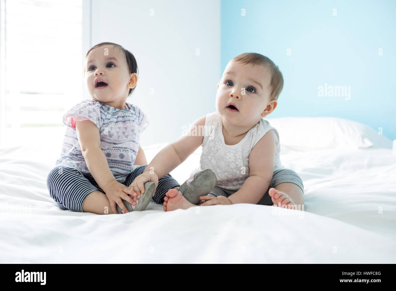 Two cute baby girls relaxing on bed in bedroom - Stock Image