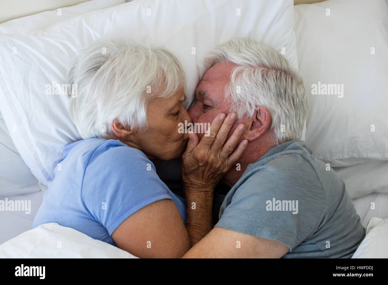 Senior couple kissing each other in bedroom at home Stock Photo