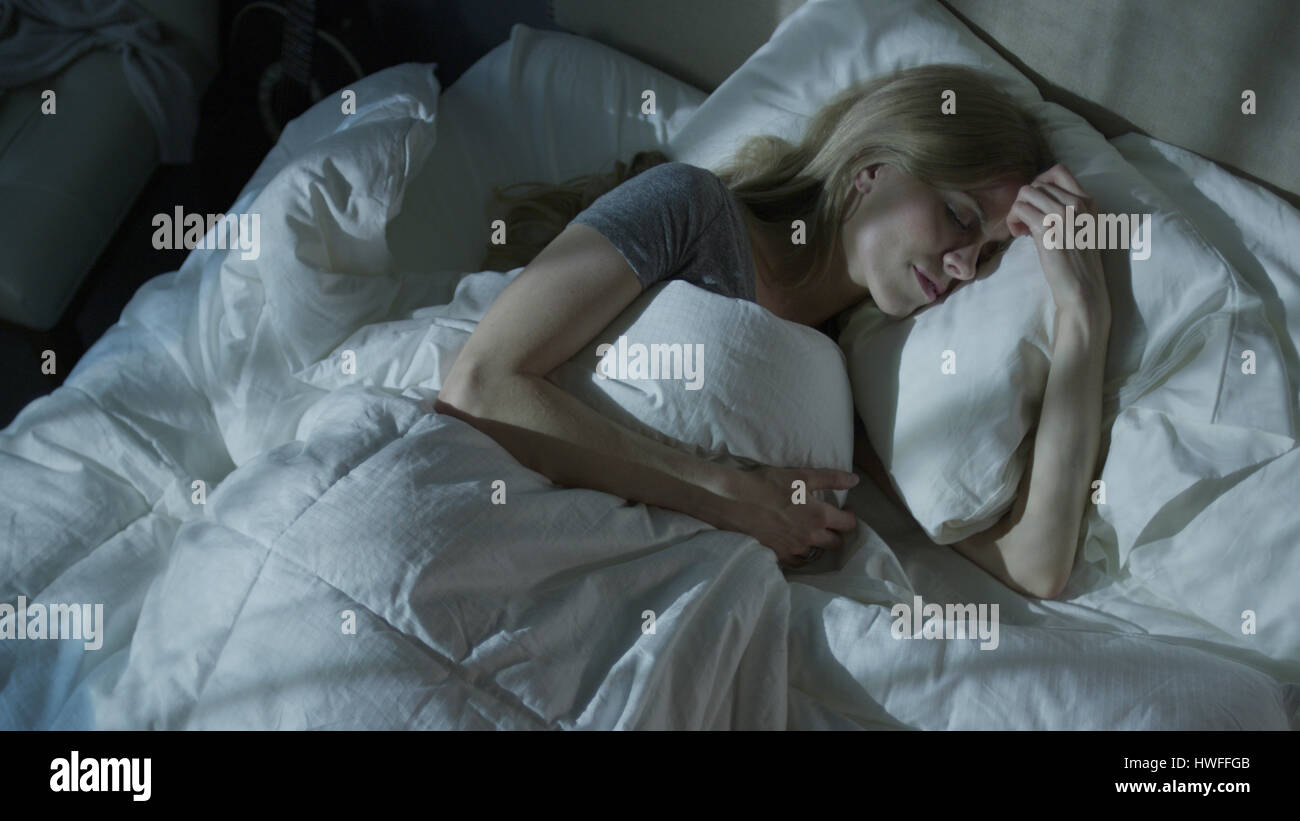 High angle view of relaxed woman dreaming and sleeping under duvet in bed - Stock Image