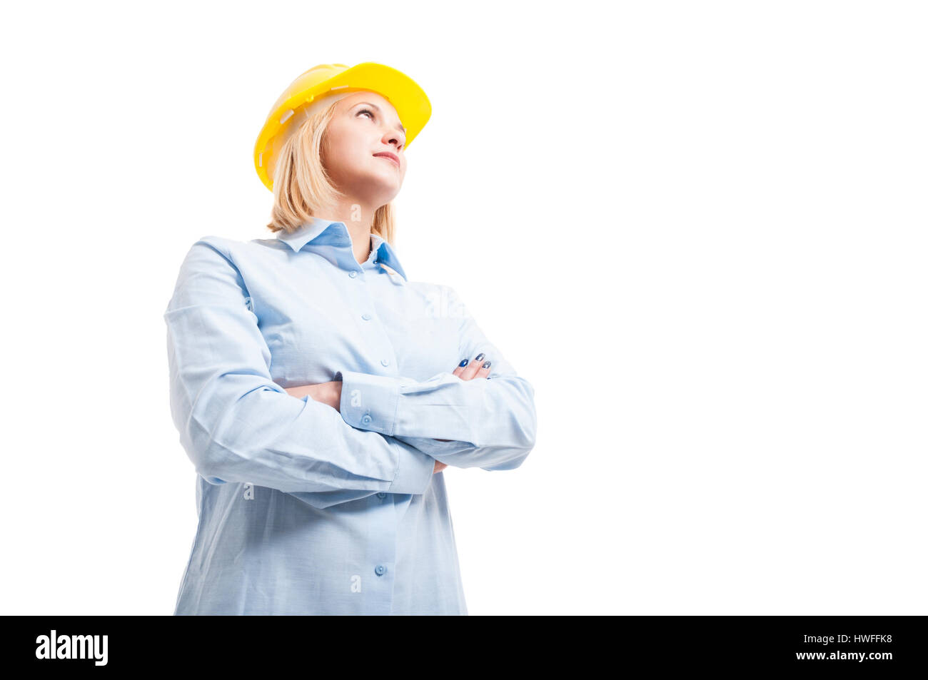 low angle hero shot of female engineer posing with arms crossed being serious isolated on white background with - Stock Image