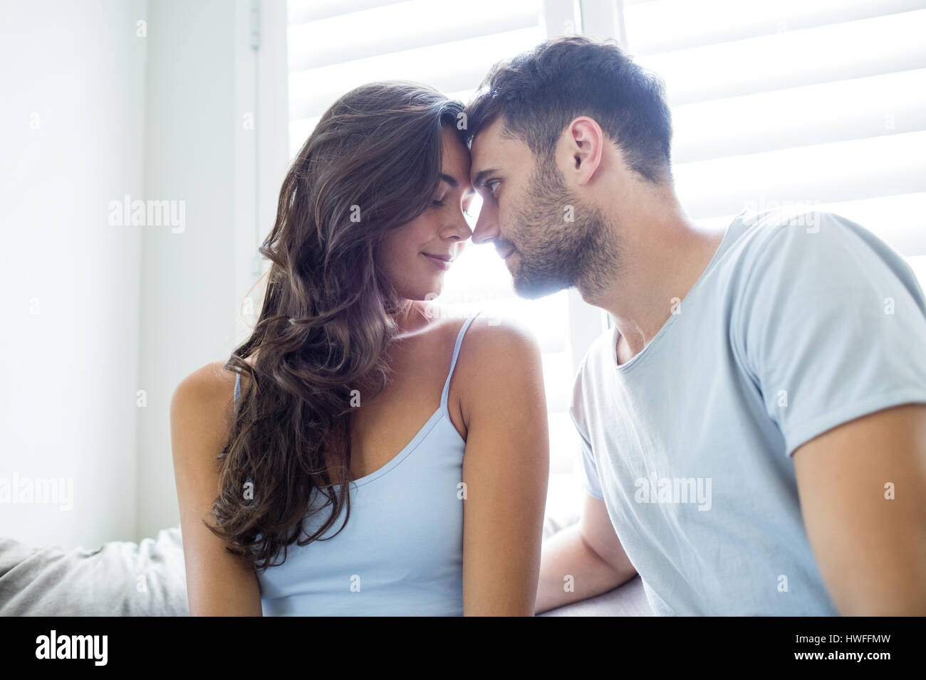 Young couple romancing in bedroom at home - Stock Image
