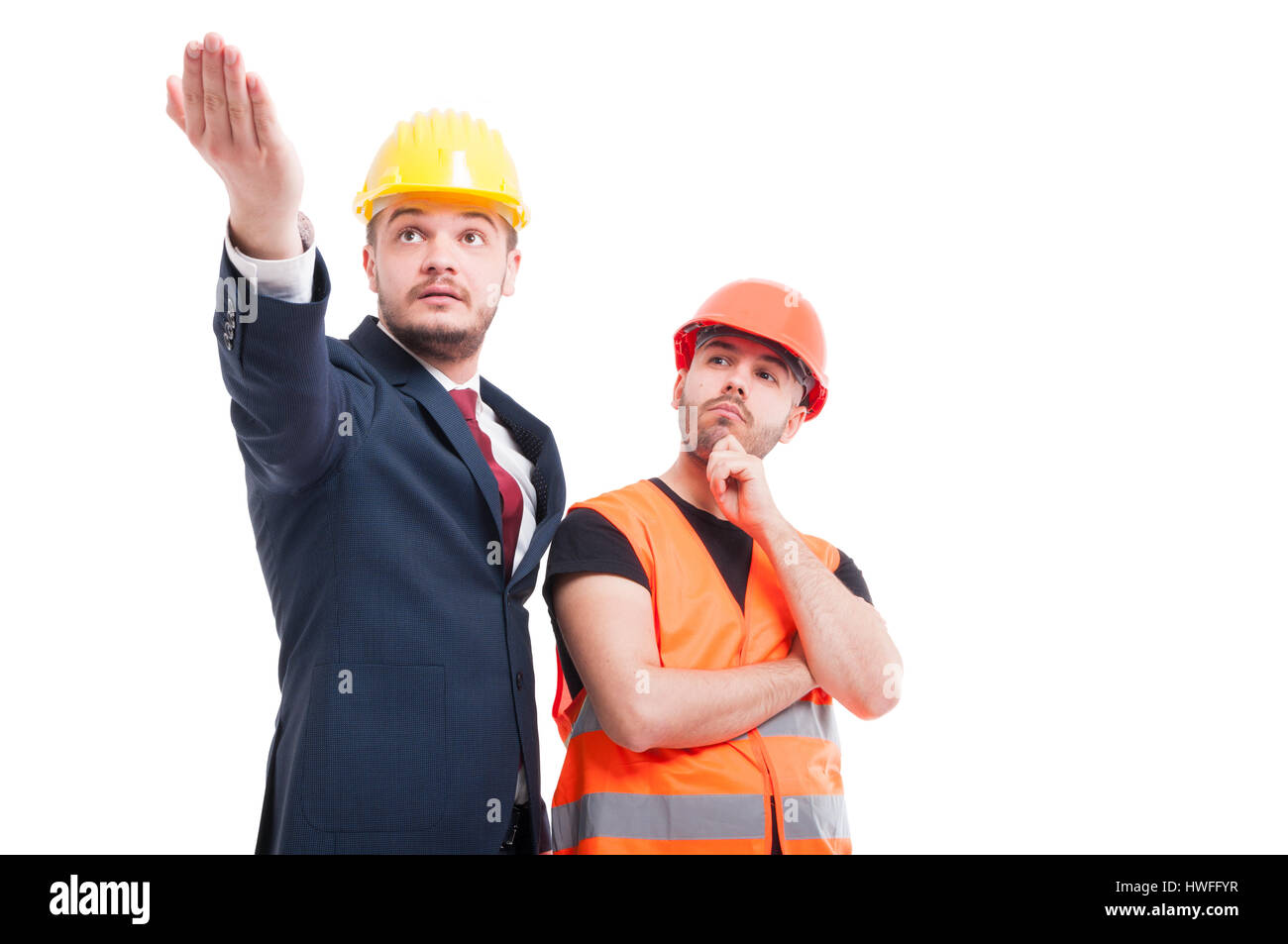 Bussinesman explaining and indicate something to young builder on white background - Stock Image