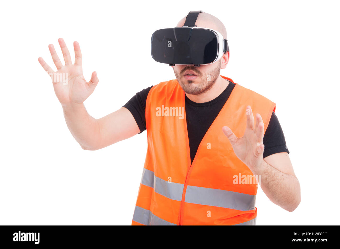 Young builder wearing vr glasses experiencing virtual gaming on white background - Stock Image