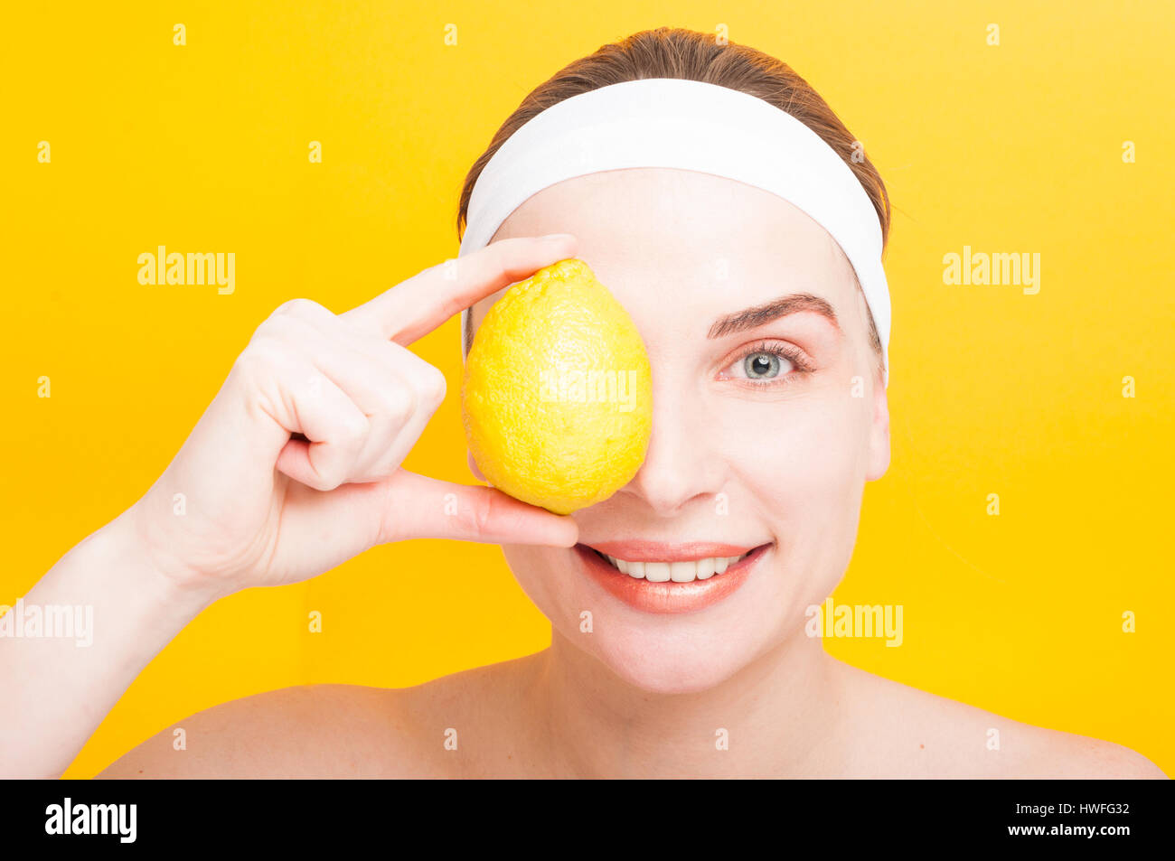 Pretty female covering her eye with a fresh lemon as purity and wellbeing concept isolated on yellow background - Stock Image