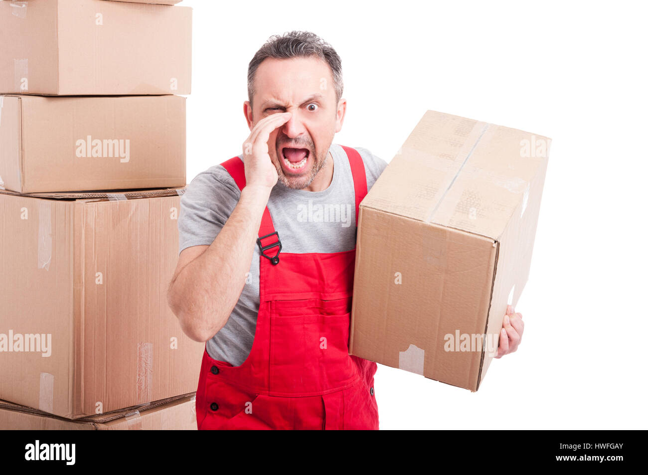 Portrait of mover man holding box and screaming loud looking very mad or angry isolated on white background - Stock Image