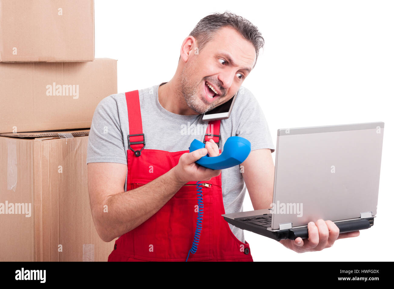 Busy mover guy multitasking with laptop and phones and yelling isolated on white background - Stock Image