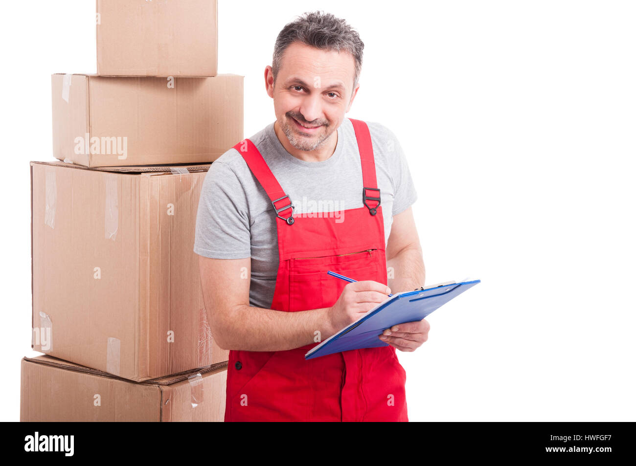 Mover guy smiling counting or writing on clipboard with cardboard boxes around isolated on white background - Stock Image