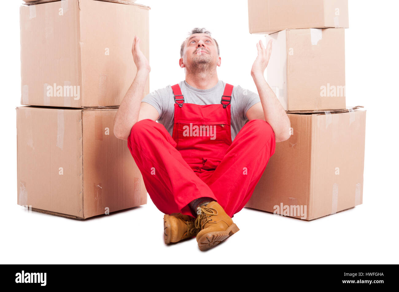 Mover man sitting down making hoping gesture looking up for a solution isolated on white background - Stock Image