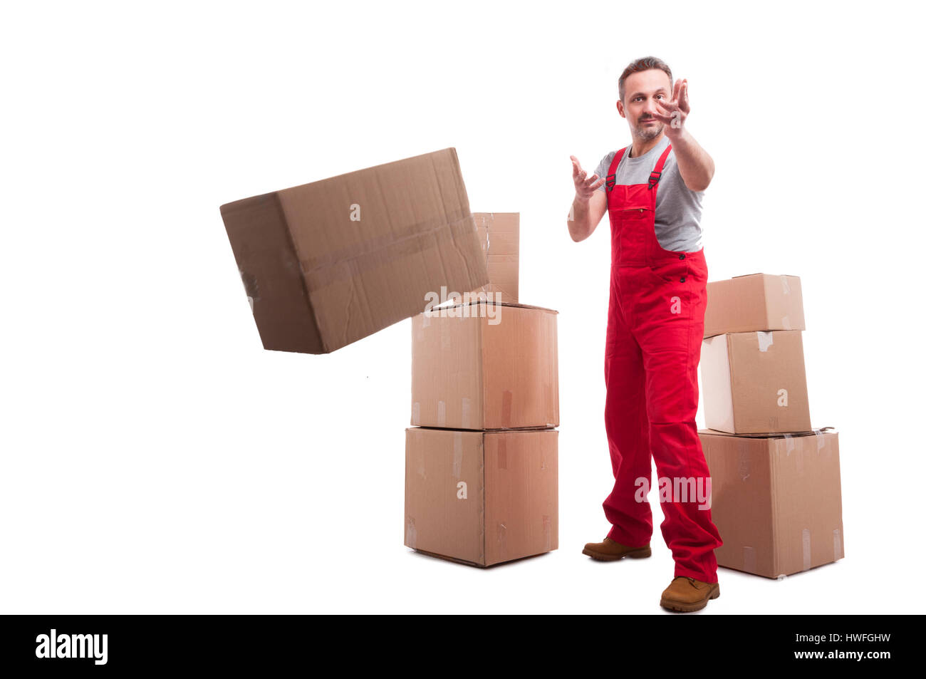 Full body mover guy throwing a cardboard box like working isolated on white background - Stock Image