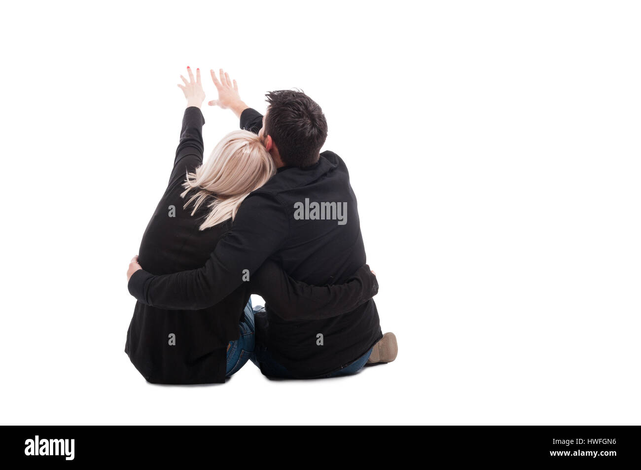 Rear view of young couple sitting down and point somewhere with copytext space isolated on white - Stock Image