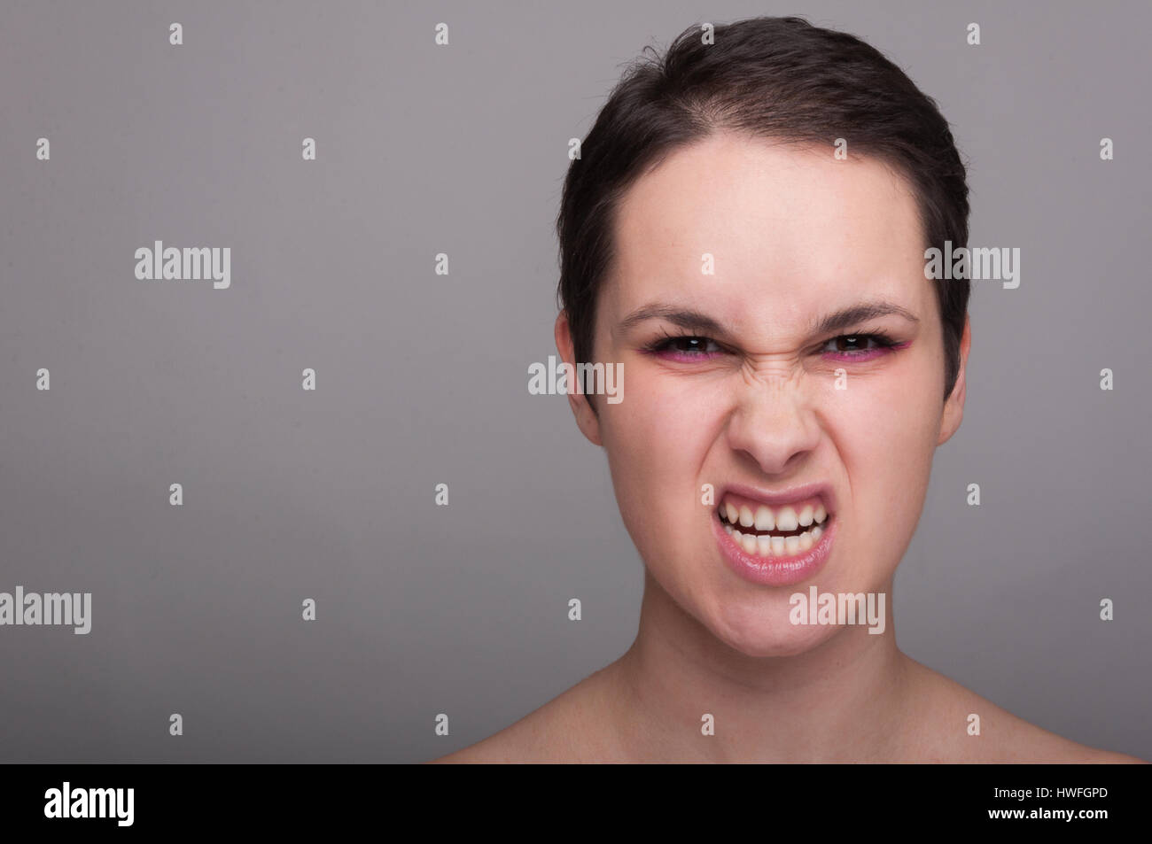 Mad young female acting rude or antisocial on gray background with copytext space - Stock Image