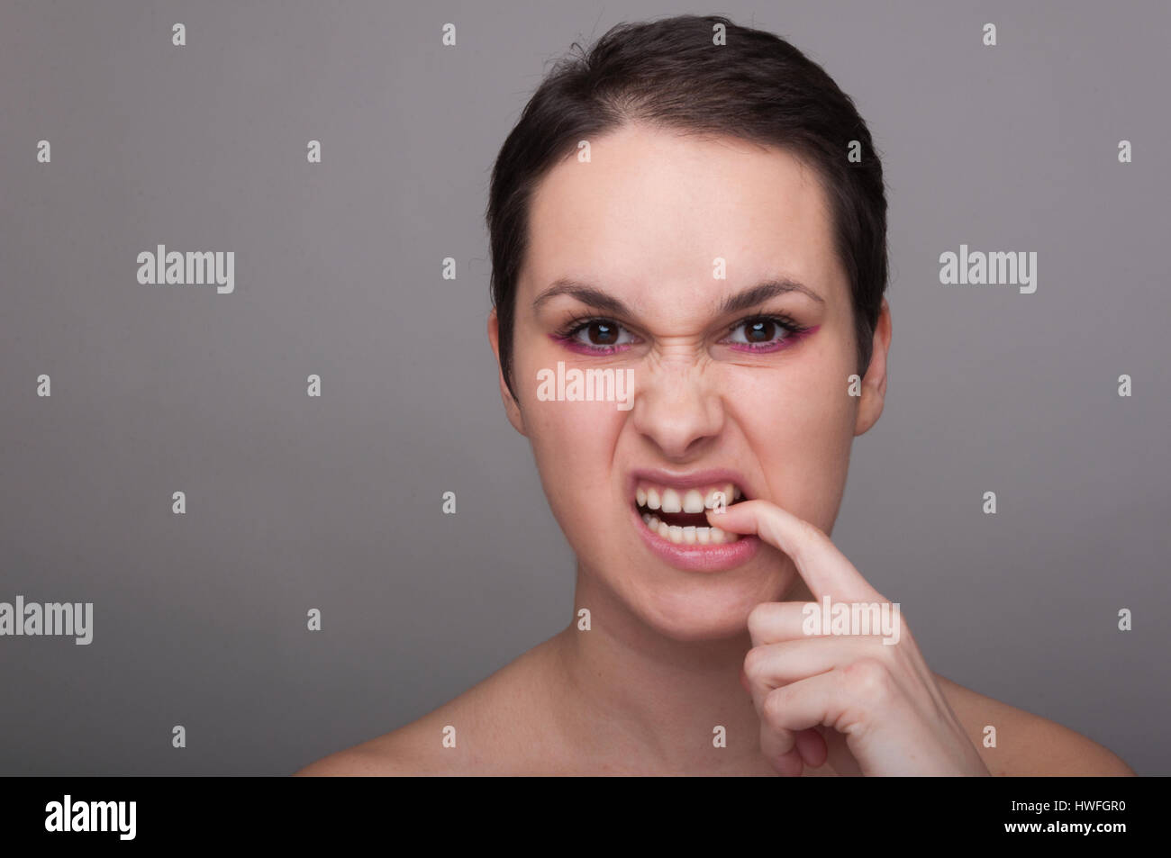 Angry or furious woman frowning and biting her finger on grey background with advertising area - Stock Image