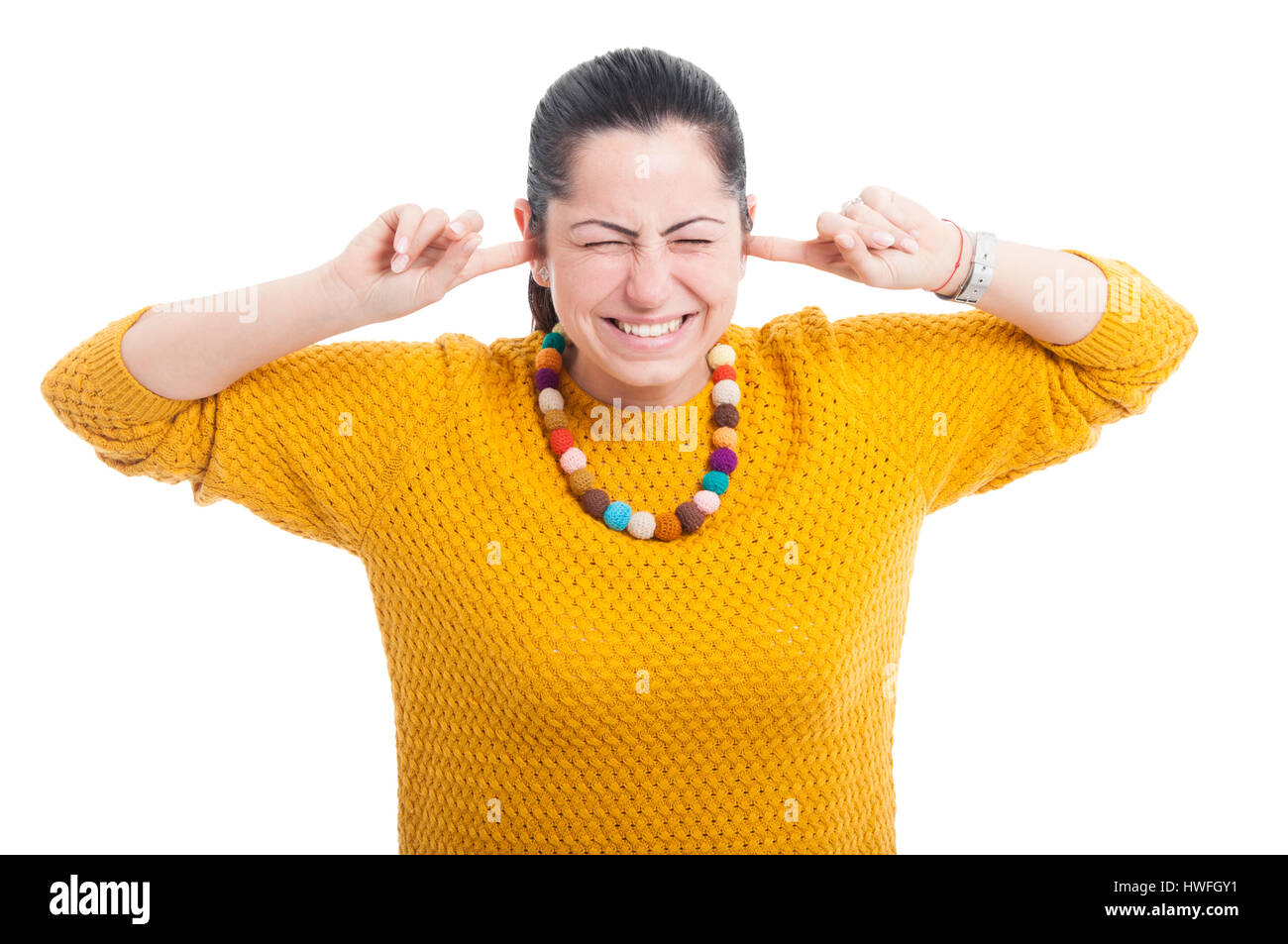Pretty woman with fingers in ears acting like a deaf on white studio background - Stock Image