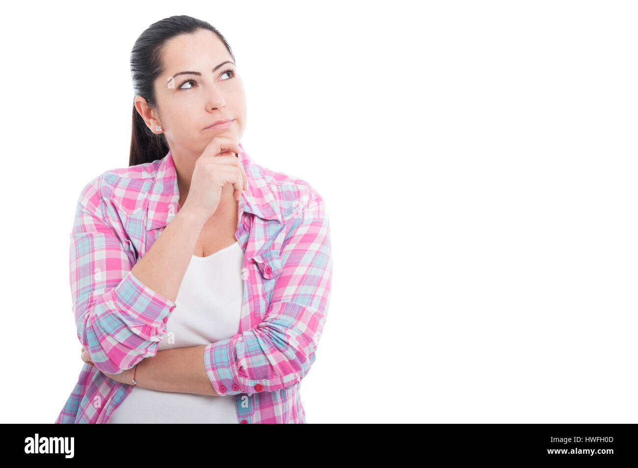 Pretty woman thinking at something with hand on chin on white background with copyspace - Stock Image