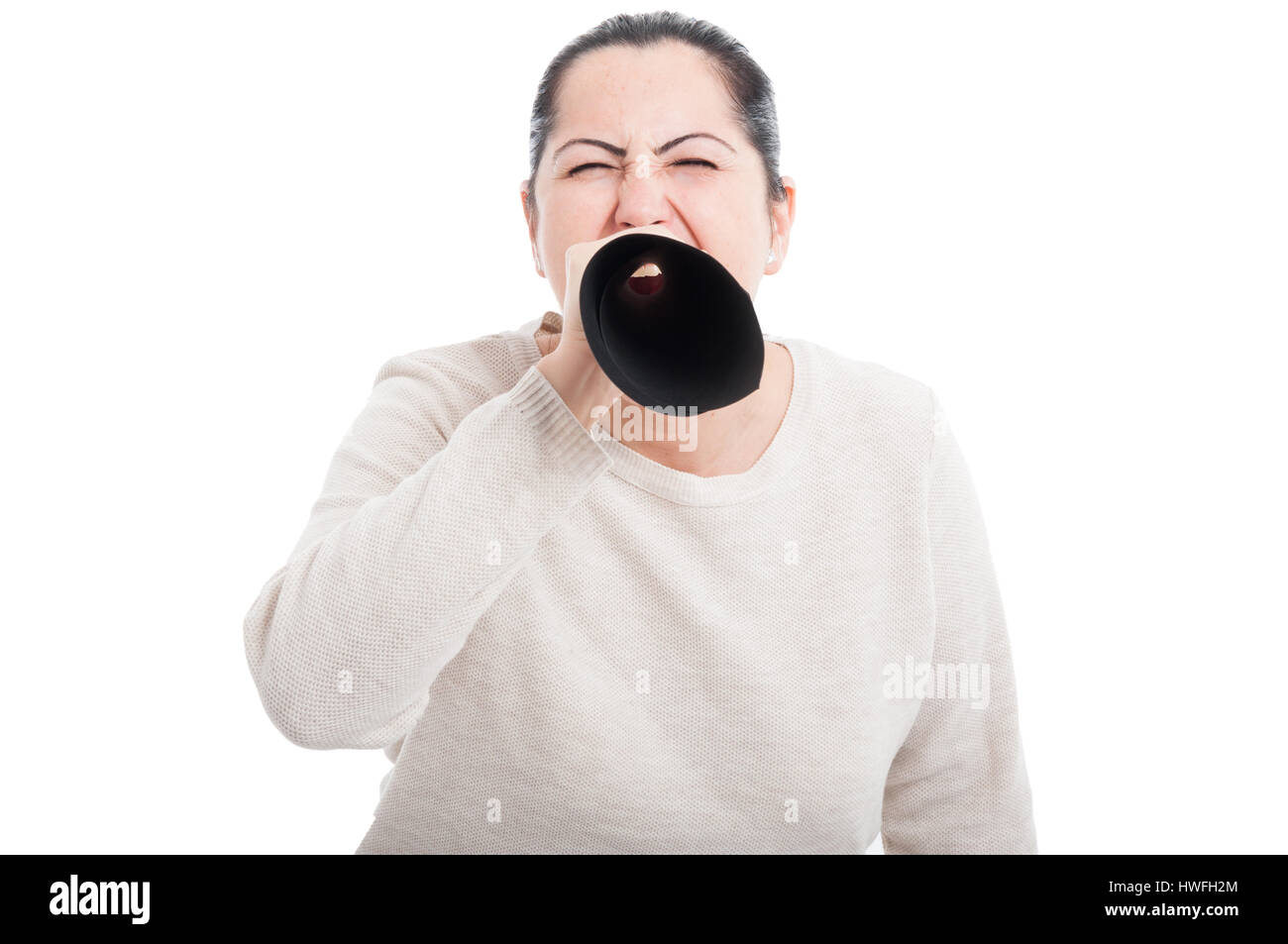 Young brunette woman talking loud through megaphone made of paper showing authority on white background - Stock Image