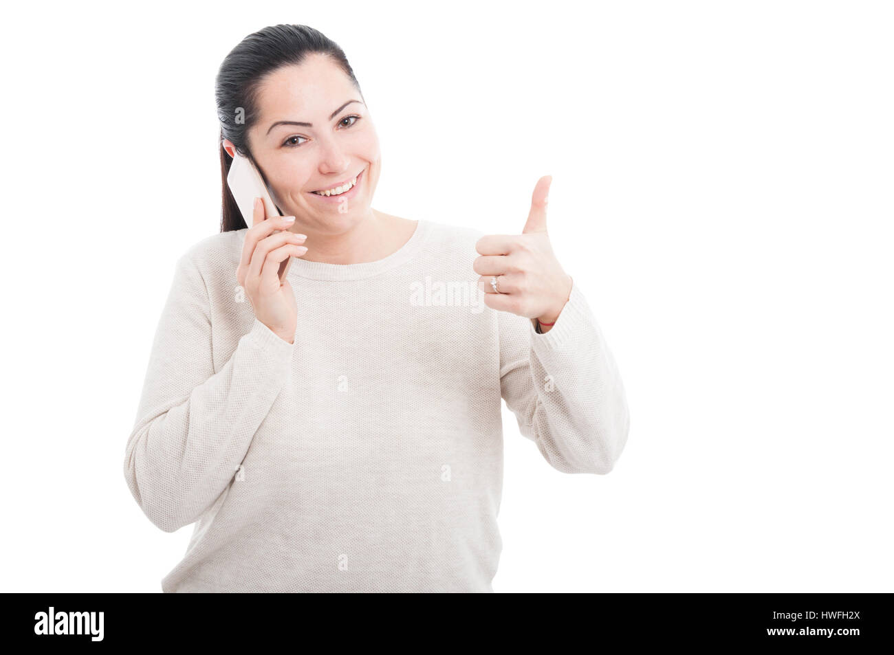Beautiful happy woman showing thumb up gesture while talking on cellphone on white background - Stock Image