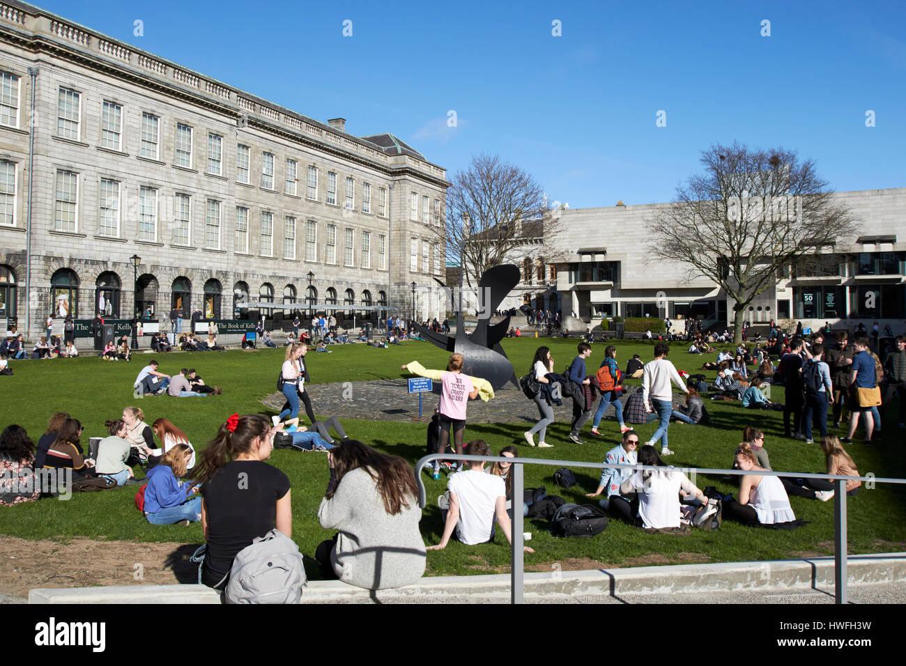 students sitting around in sunshine on fellows square trinity college Dublin Republic of Ireland - Stock Image