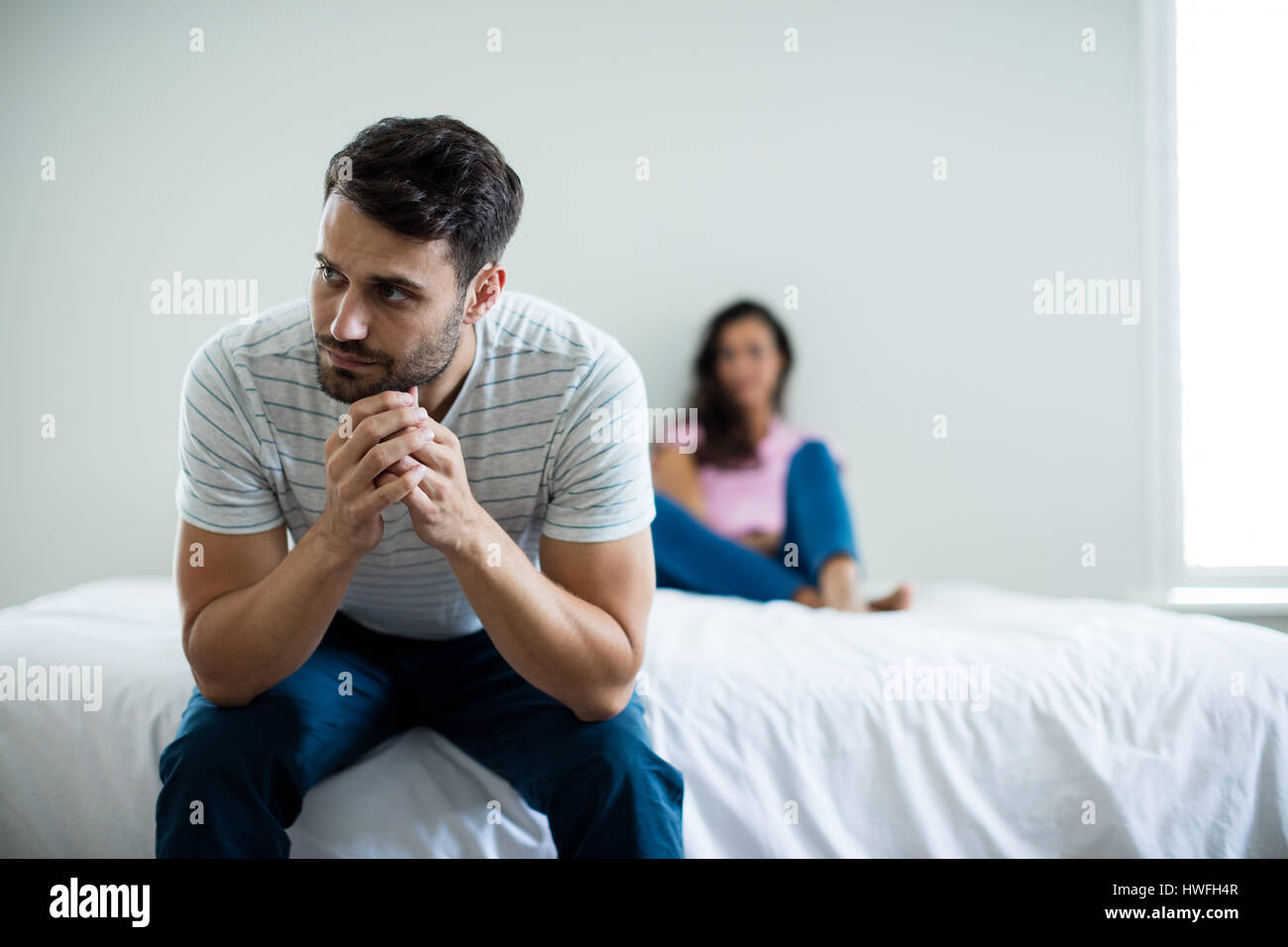 Couple ignoring each other in bedroom at home - Stock Image