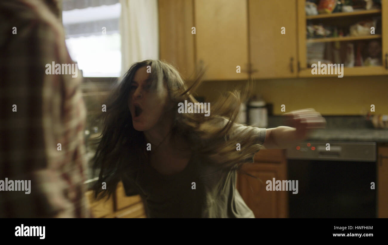 Selective focus blurred view of angry girlfriend shouting at boyfriend in kitchen - Stock Image