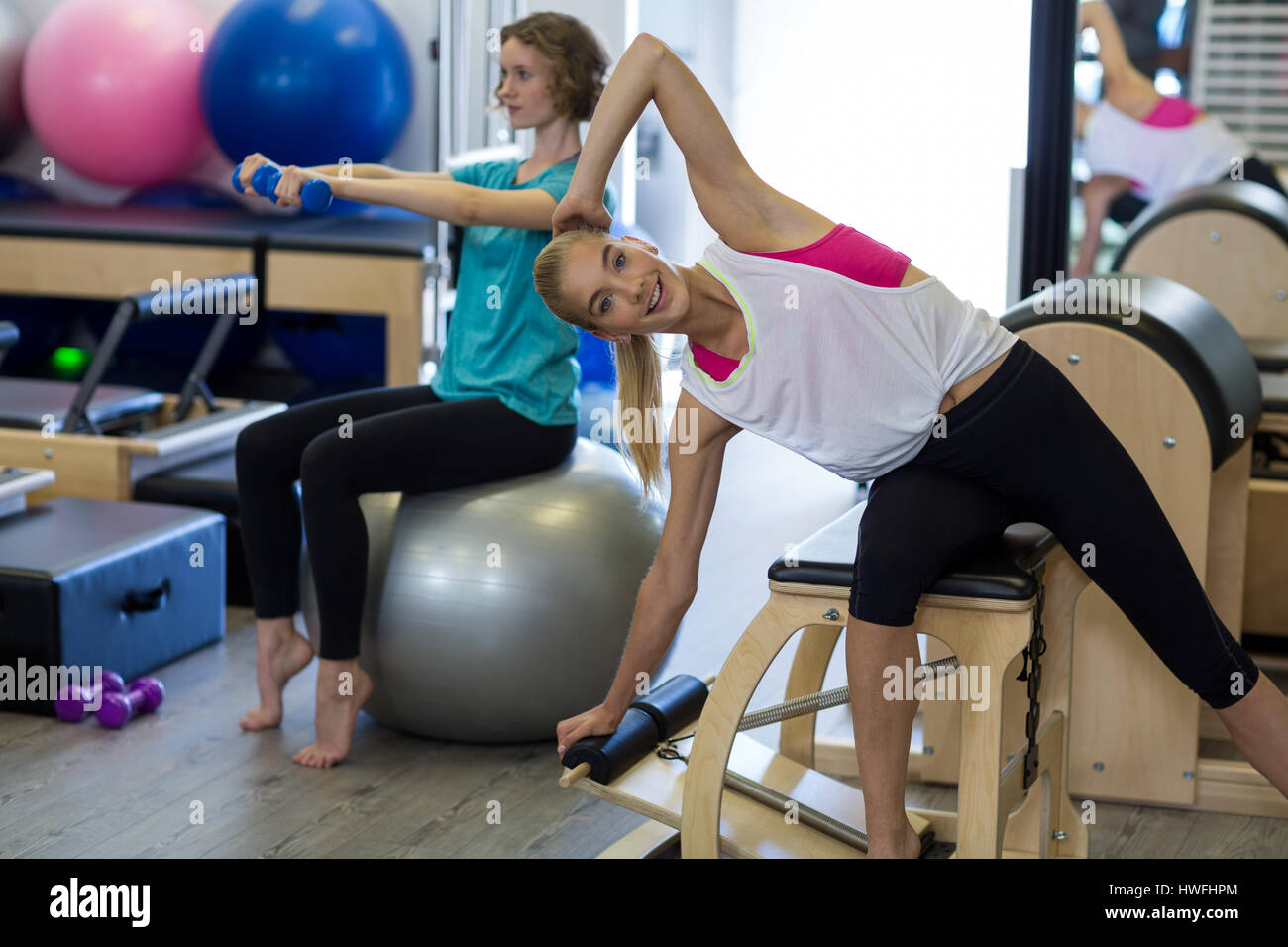 Woman exercising on reformer in gym - Stock Image