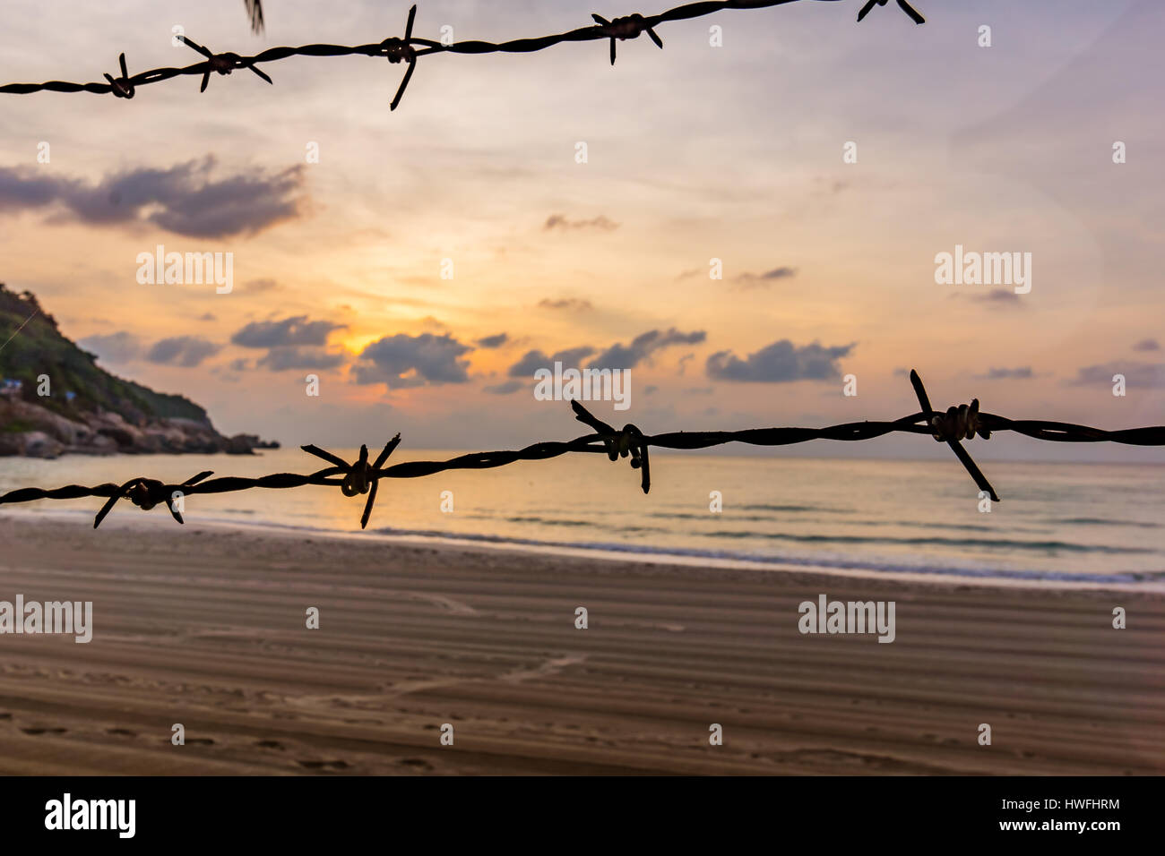 An unknown raked sandy beach with barbed wire against refugees? - Stock Image