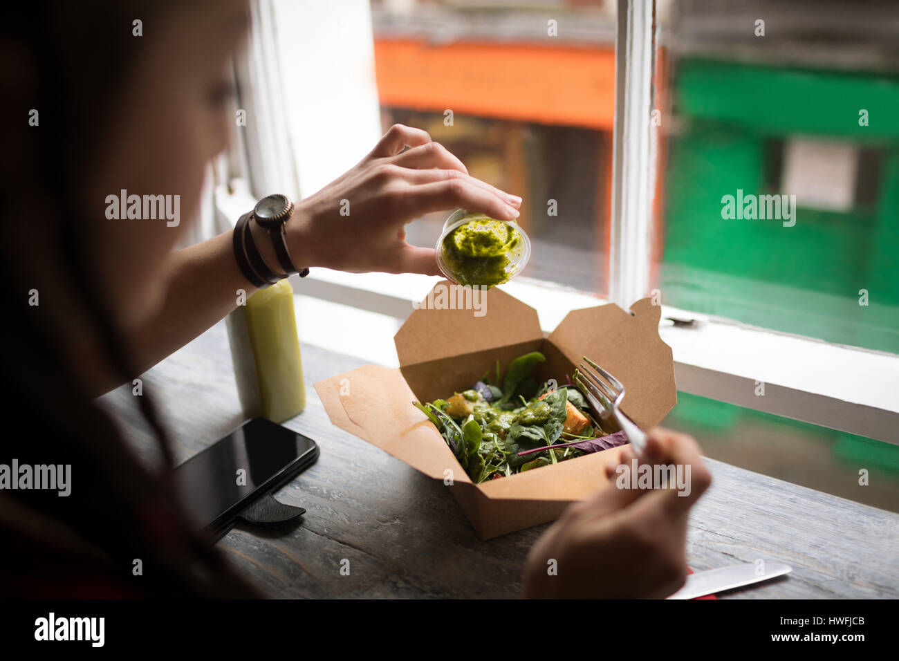 Woman pouring green sauce on a salad in café - Stock Image