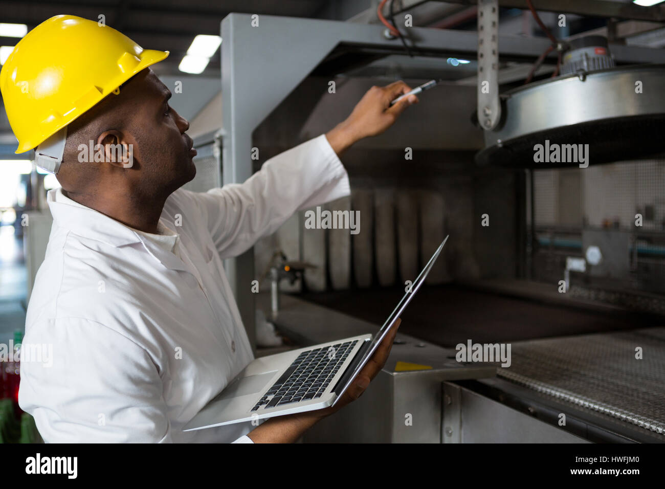 Male worker wearing lab coat while using laptop in juice factory - Stock Image